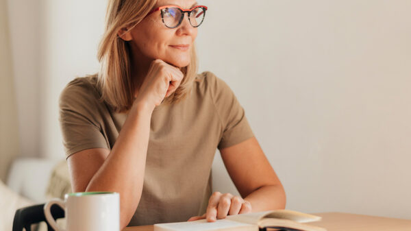 Best books on charisma - a woman reading with a cup of tea.