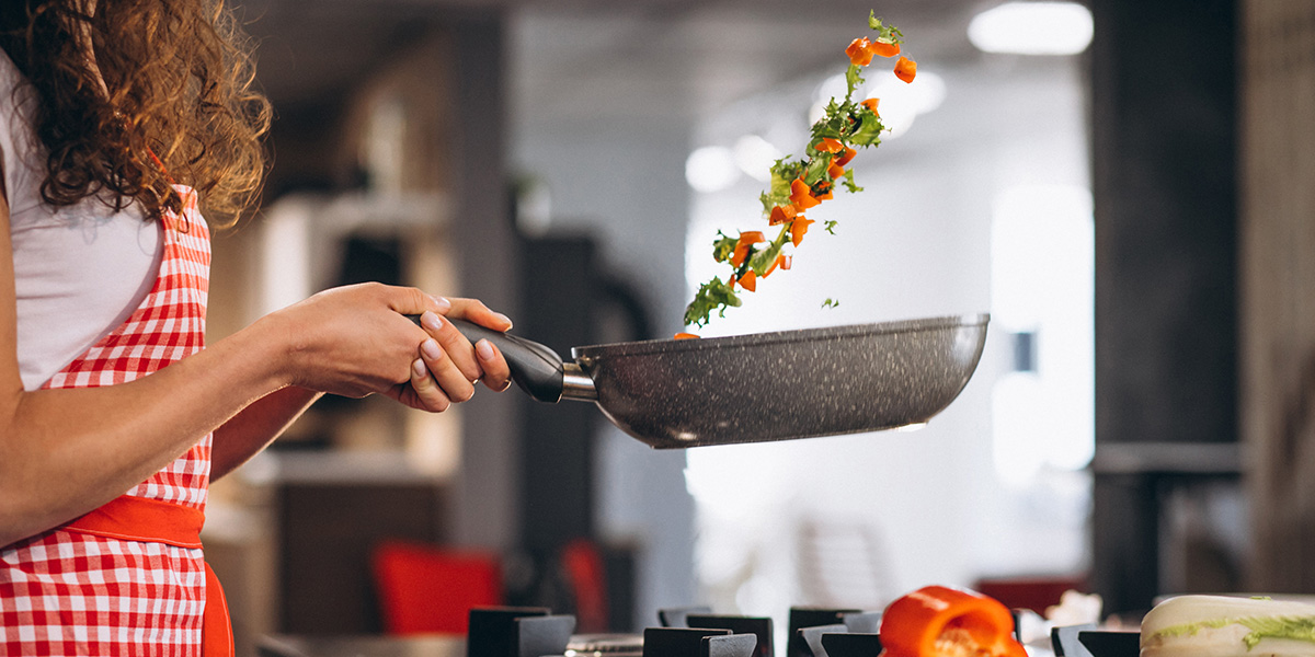 A woman chef cooking with a pan.