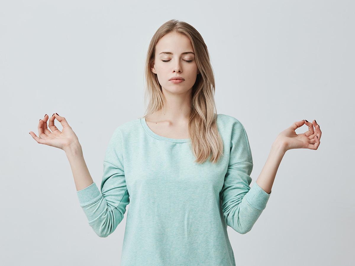 A woman meditating and finding balance.