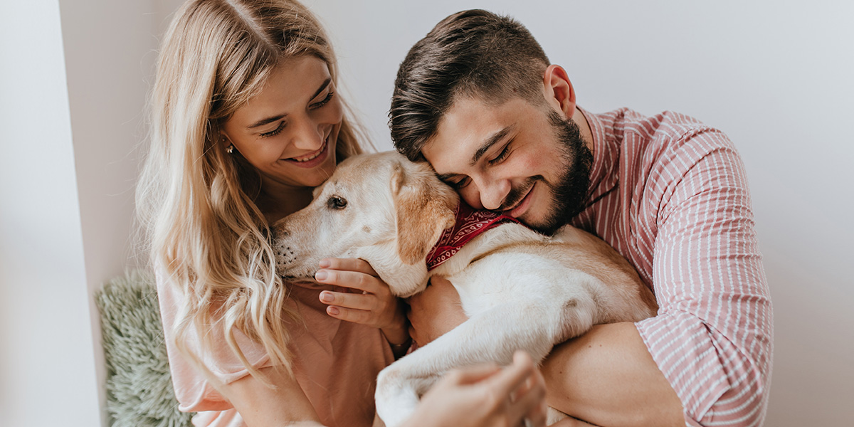 A couple hugging their dog.