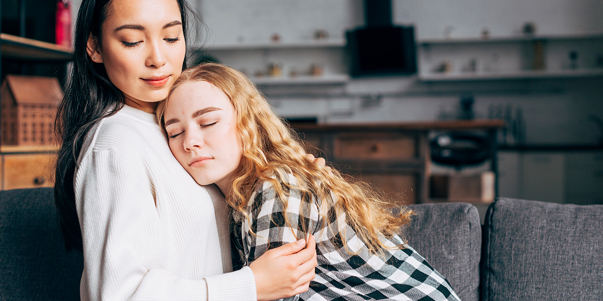 A young woman consoling her friend.