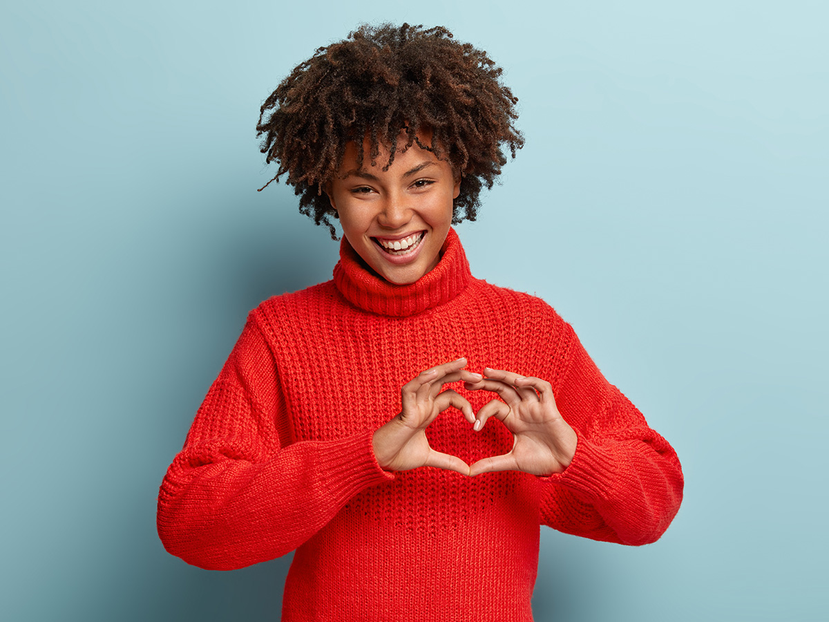 How to make people like you instantly - a young girl holding a heart sign.