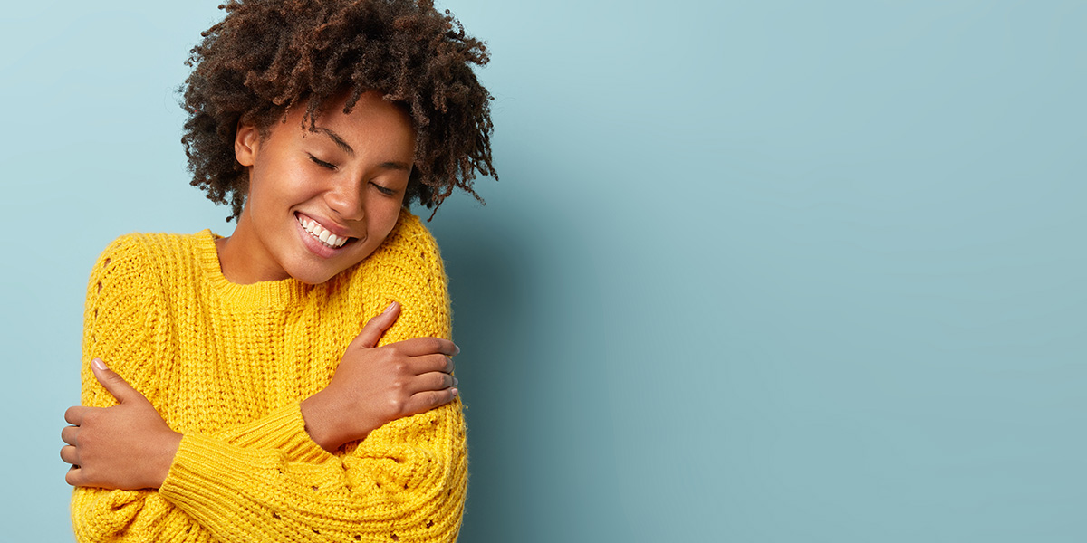 A girl hugging herself.