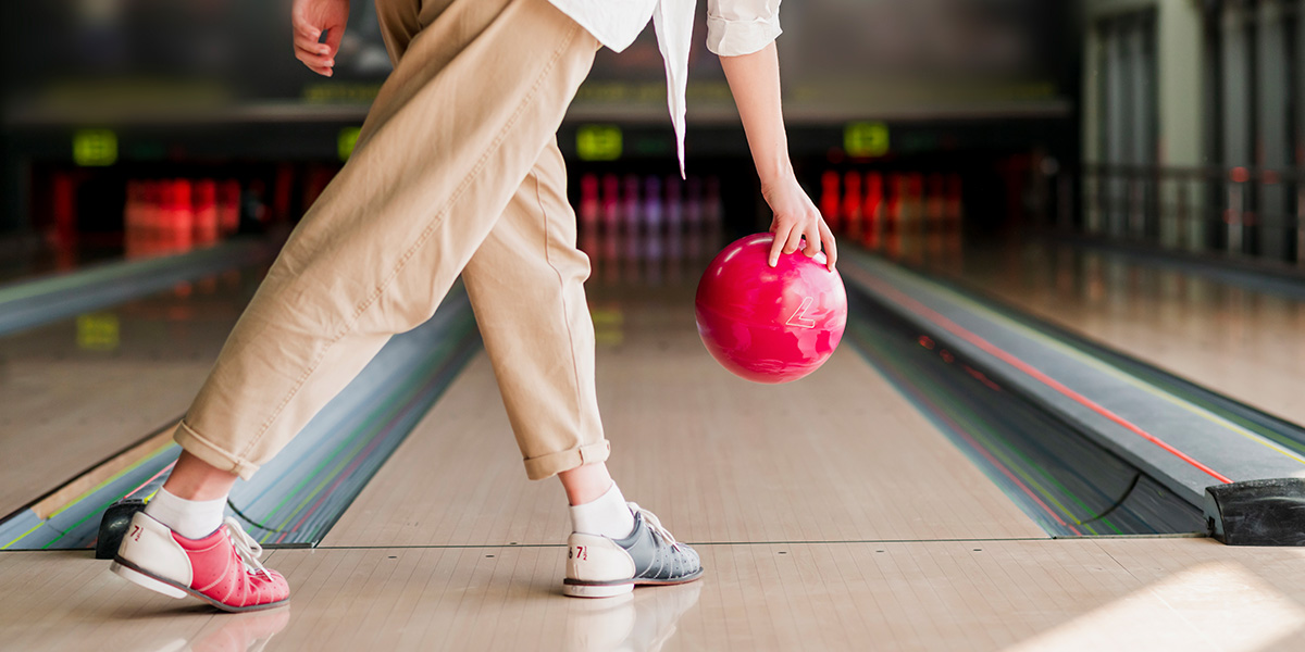 A girl trying to improve her aim in bowling.