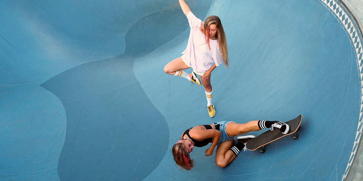 Two girls in a blue skatepark.
