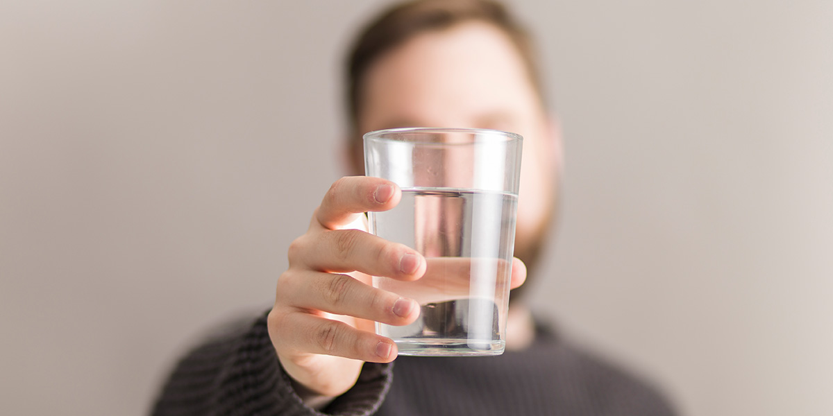 Man holding a glass of water.