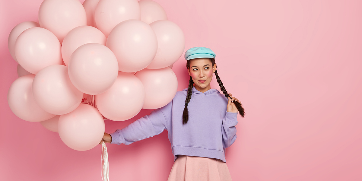 A girl with pink balloons and blue hat