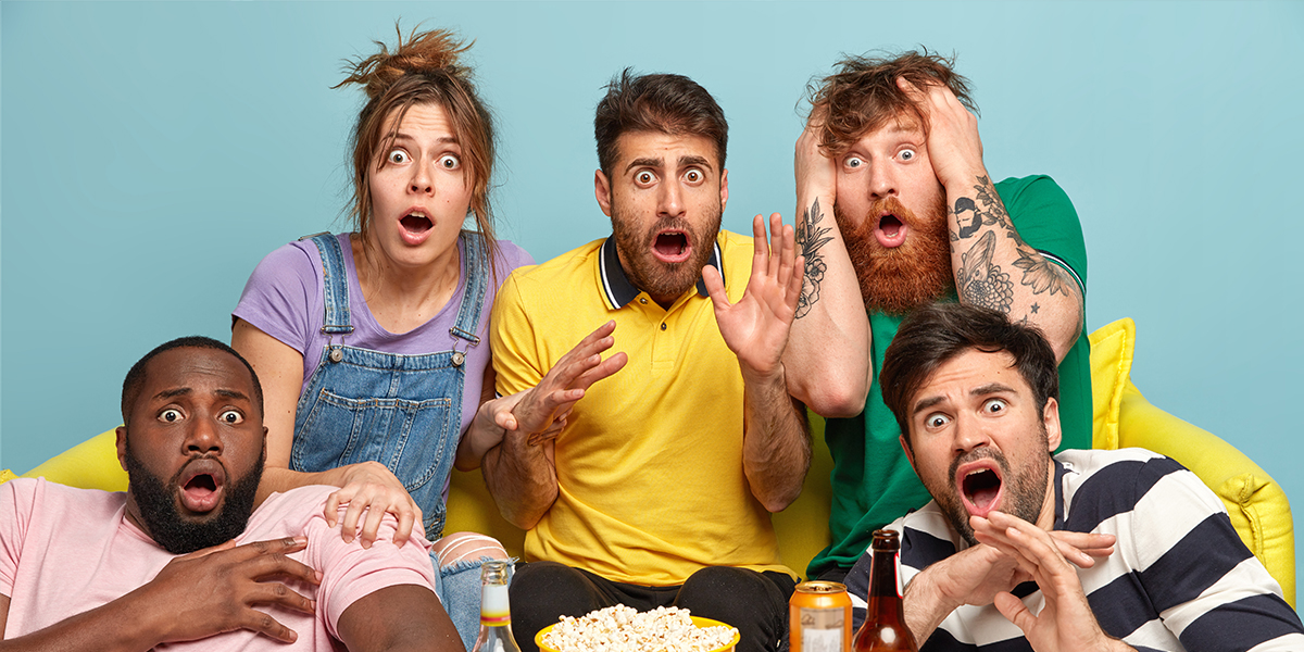 Group of friends watching funny horror movie